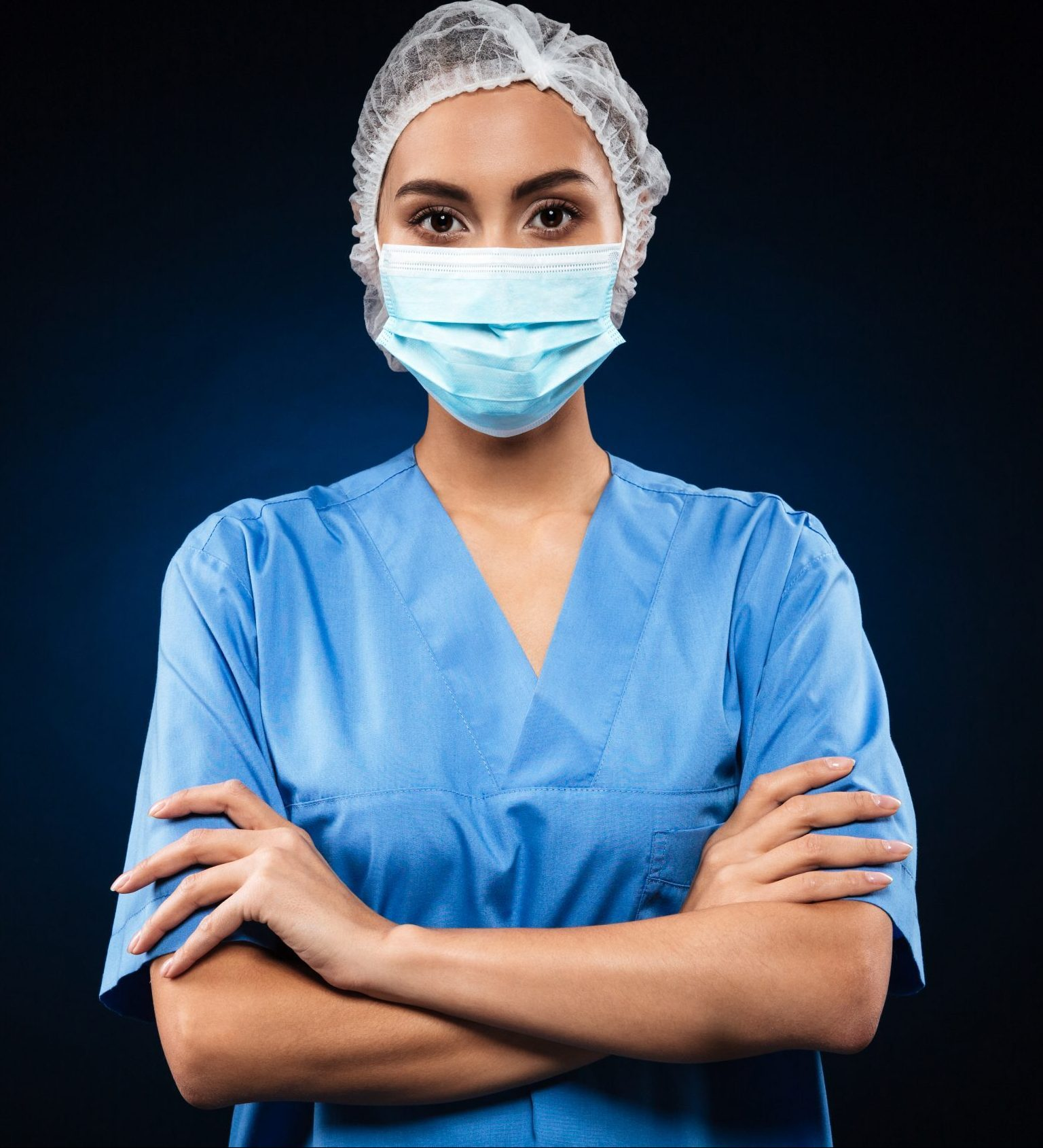 Serious doctor in medical mask and cap looking camera and holding hands folded isolated over black